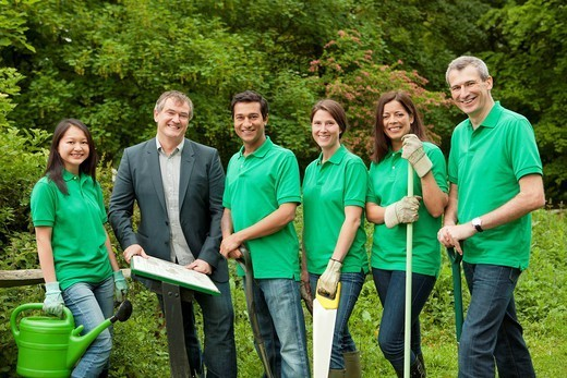 Gardeners with businessman in park : Stock Photo