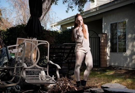 Woman standing in dilapidated backyard : Stock Photo