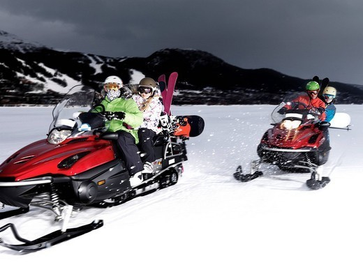 Two couples riding skidoos. : Stock Photo