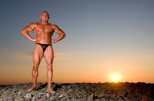 Bodybuilder Poses at Sunset. : Stock Photo