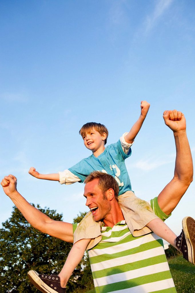 Stock Photo: 1773-55538 Father With Son on Shoulders Cheering