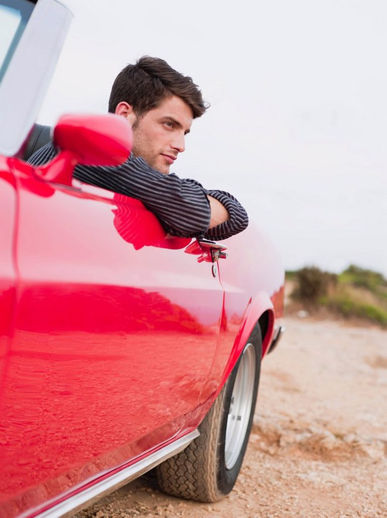 man leaning out of an open_topped car : Stock Photo
