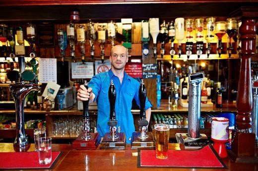 Bartender posing in british pub interior. : Stock Photo