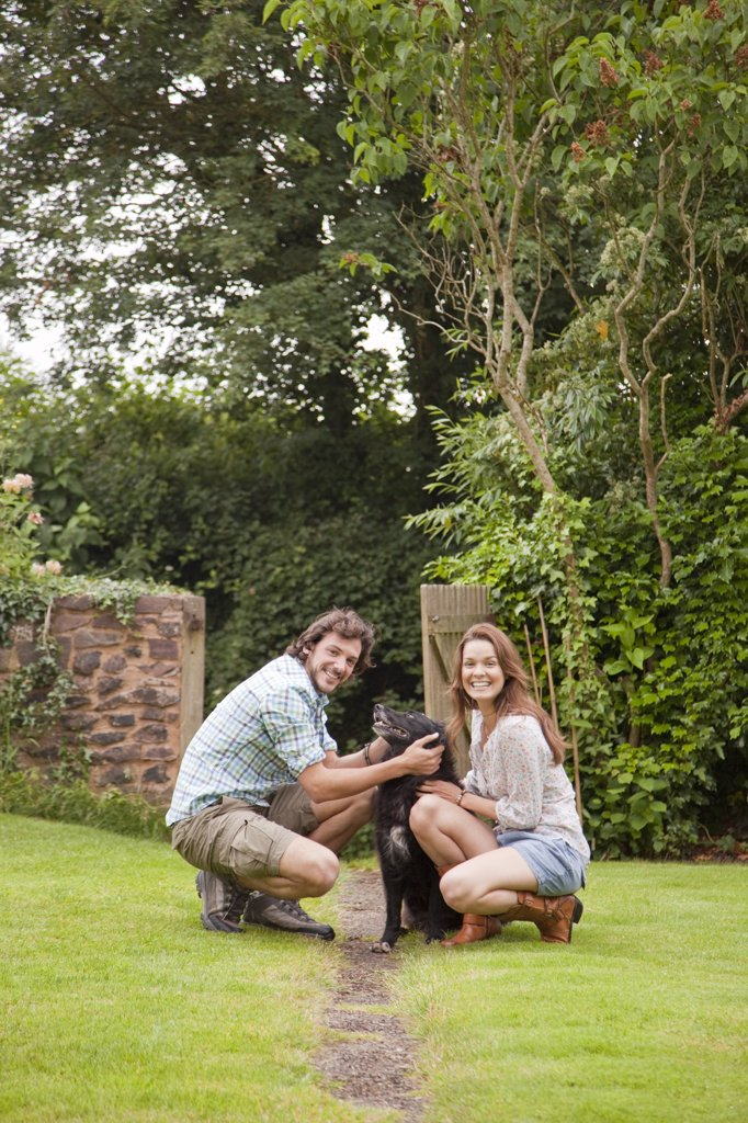 couple in garden with dog : Stock Photo