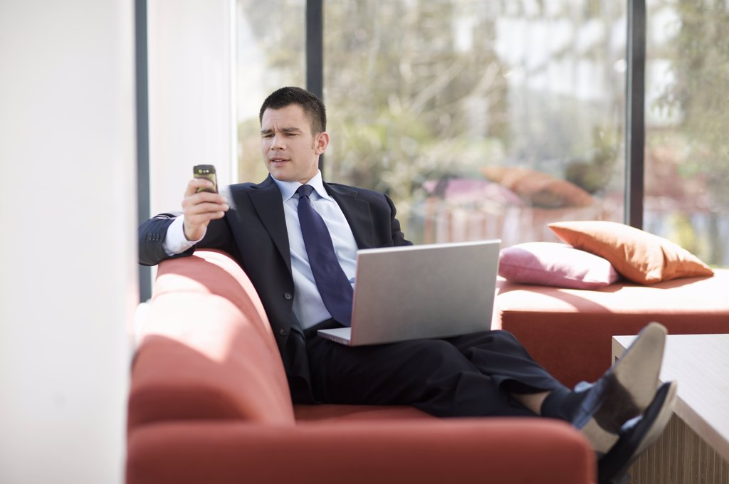 Businessman with laptop on sofa : Stock Photo
