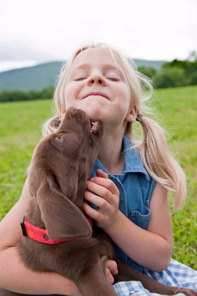 Stock Photo: 1773-56518 Young girl hugging her puppy