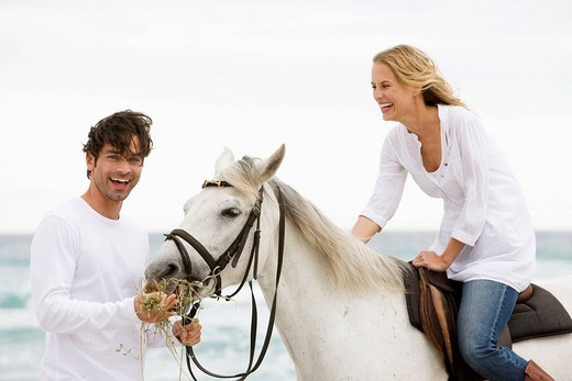 White horse, man ,woman, beach, sea, sand : Stock Photo
