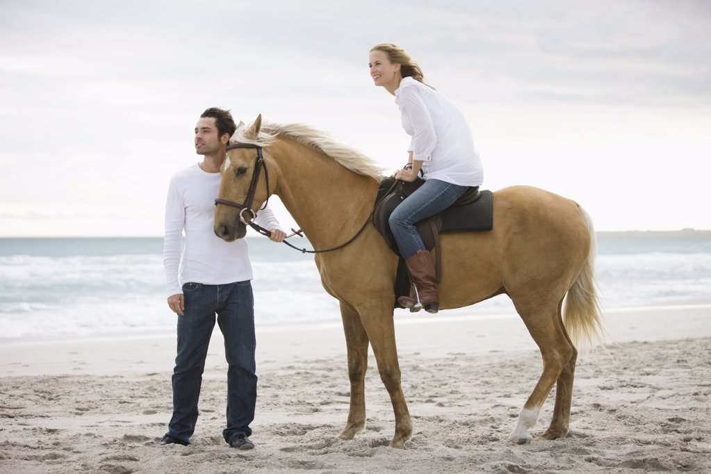 Brown horse, man, woman, beach, sea, sand : Stock Photo