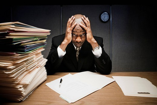 Businessman at desk with pile of folders : Stock Photo