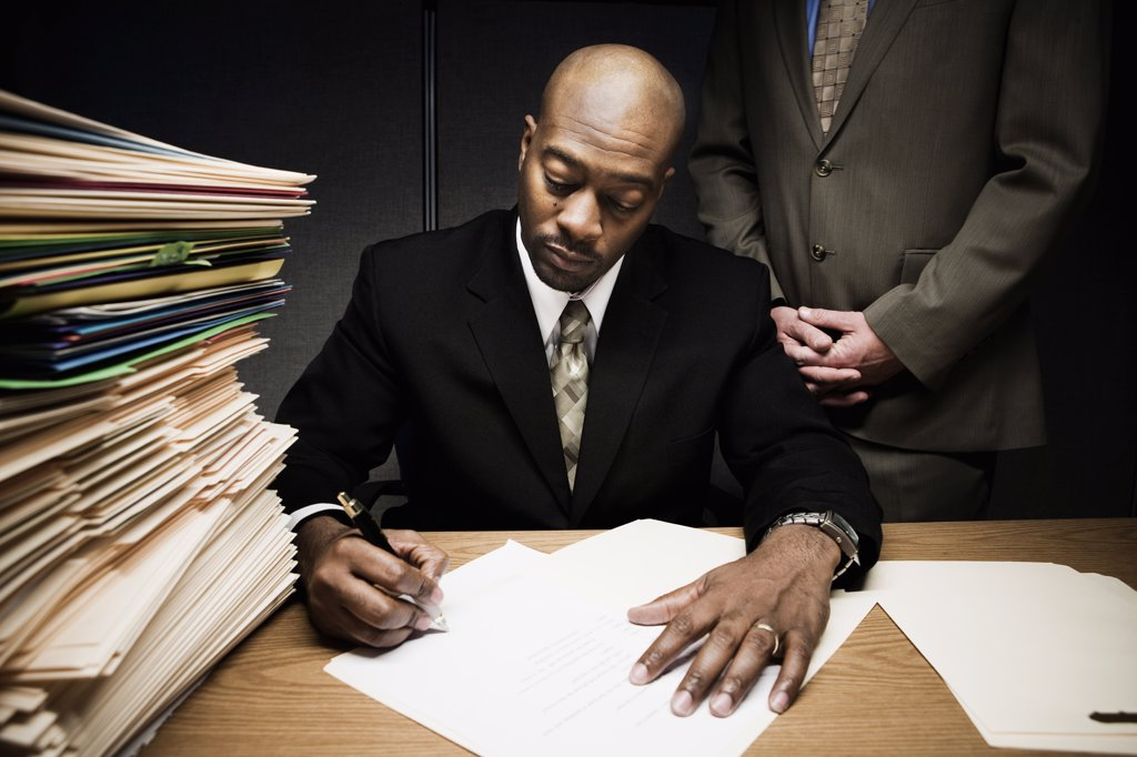 Man doing paperwork with man behind him : Stock Photo