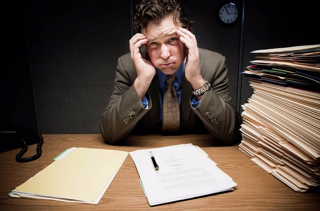 Stressed man at desk with paperwork : Stock Photo