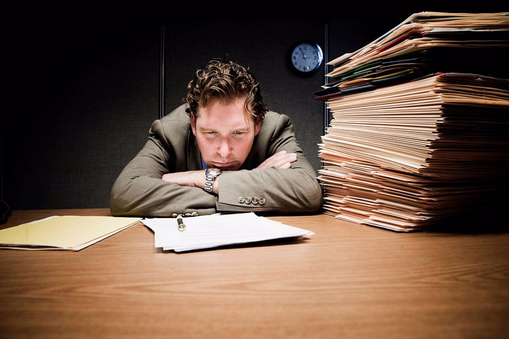 Stressed man with head down on desk : Stock Photo