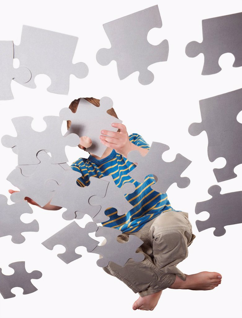 Stock Photo: 1773-56957 Boy playing with oversize jigsaw puzzle