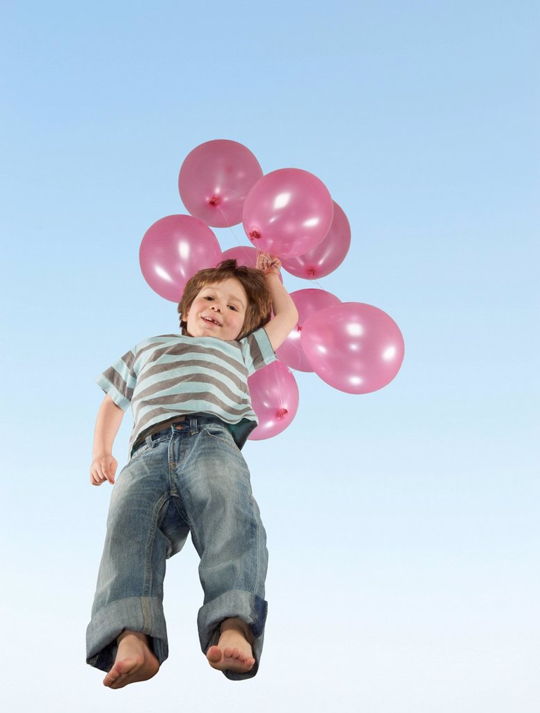Boy jumping with bunch of balloons : Stock Photo
