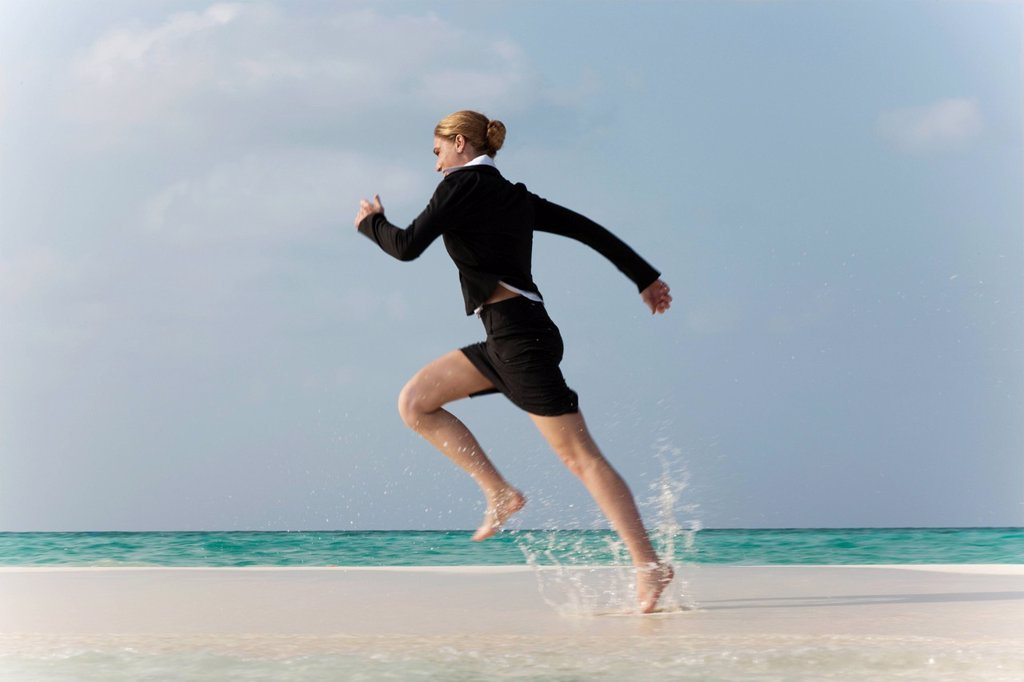 Businesswoman running on tropical beach : Stock Photo