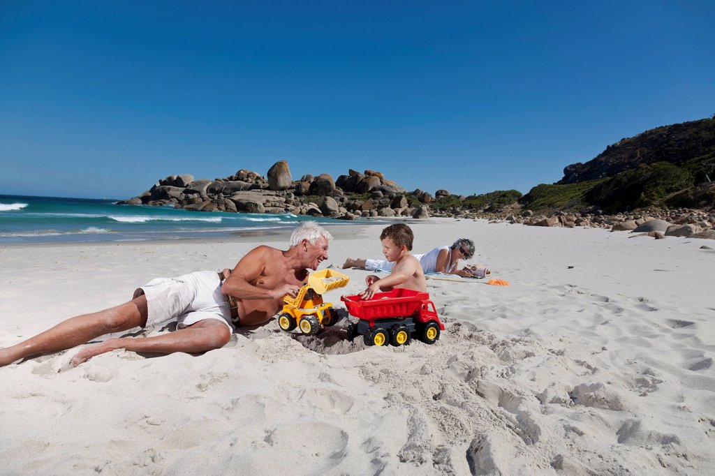 Man playing with grandson on beach : Stock Photo
