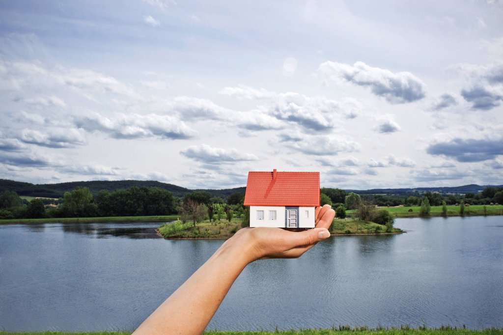 Woman holding model house at lake : Stock Photo
