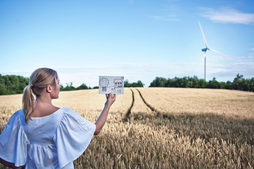 Stock Photo: 1773-57270 Woman examining child's drawing in field
