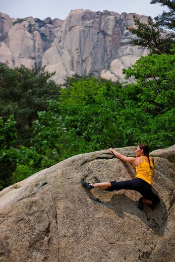 Woman climbing rocky mountainside : Stock Photo