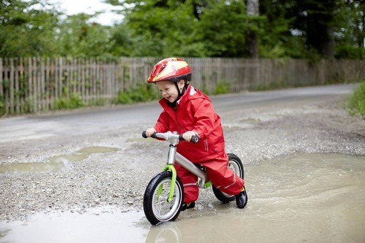 Smiling boy riding bicycle in puddles : Stock Photo