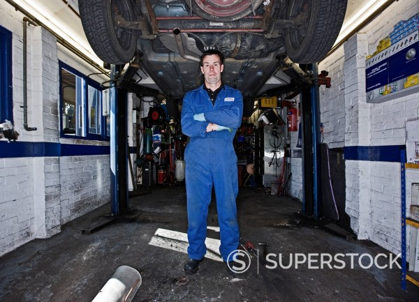 Stock Photo: 1773-57892 Mechanic standing under lifted car