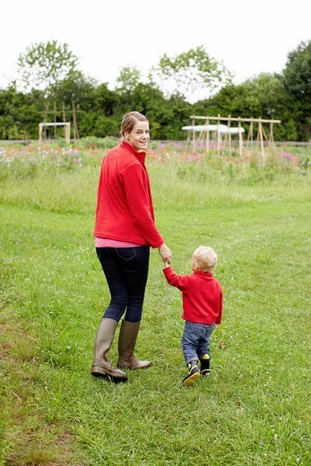 Mother and son walking in field : Stock Photo