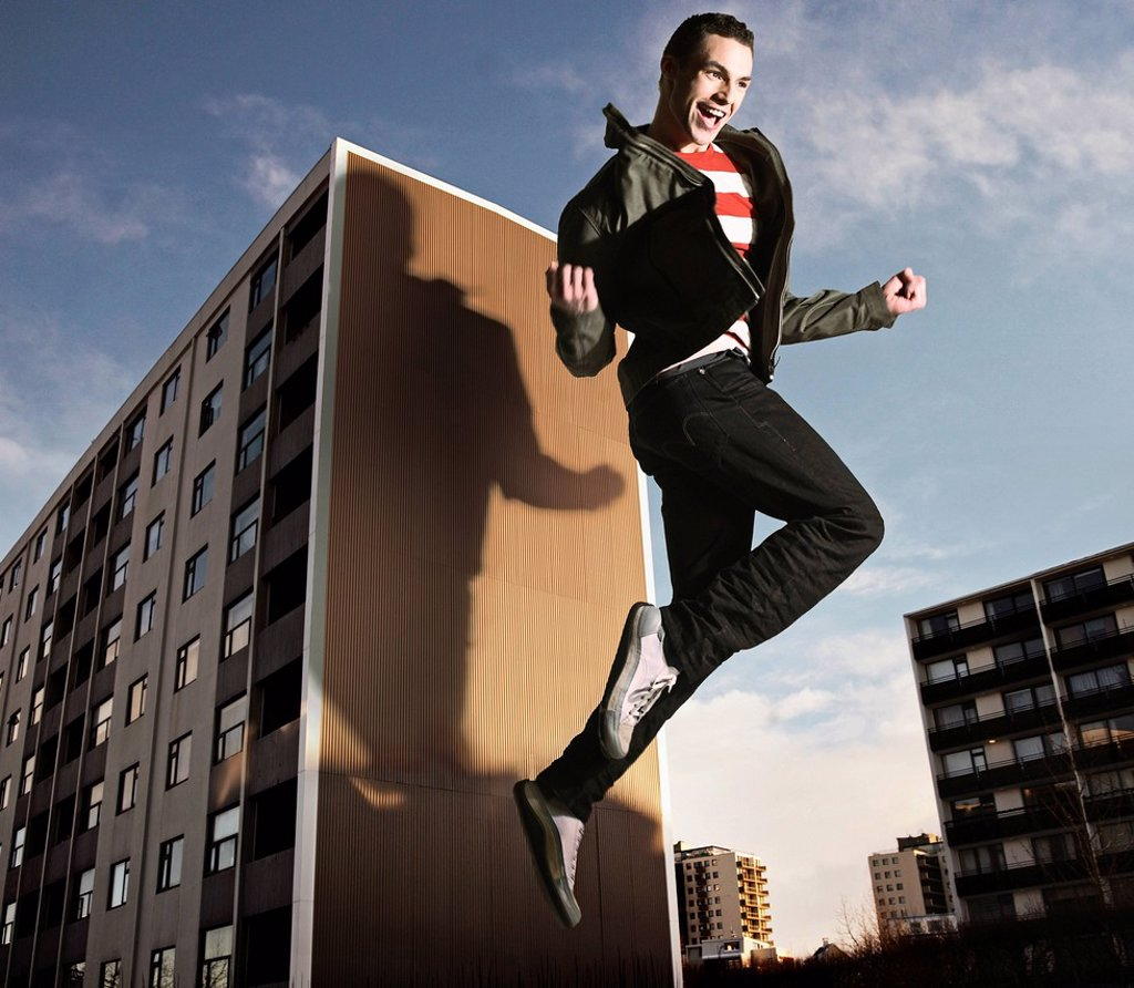 Oversized man jumping by building : Stock Photo