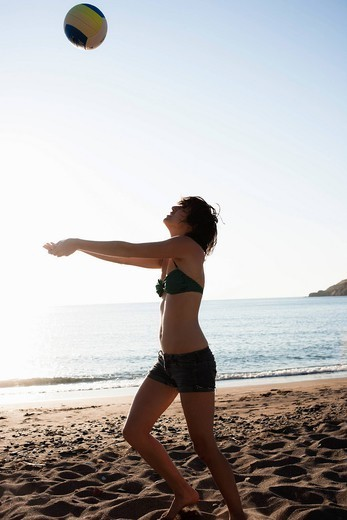 Woman playing with volleyball on beach : Stock Photo
