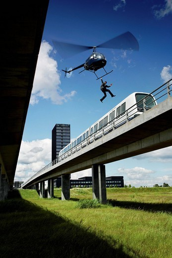 Man jumping from helicopter to train : Stock Photo