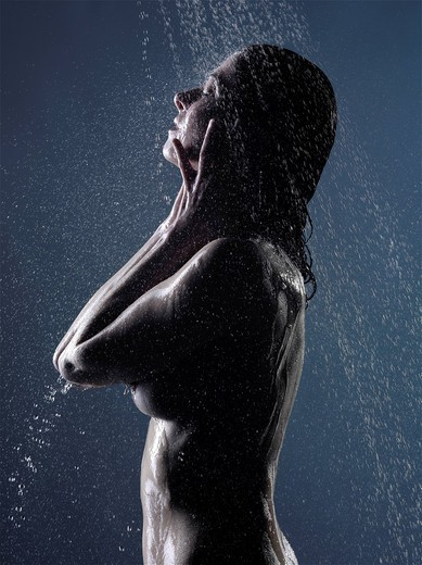 Woman washing her face in shower : Stock Photo