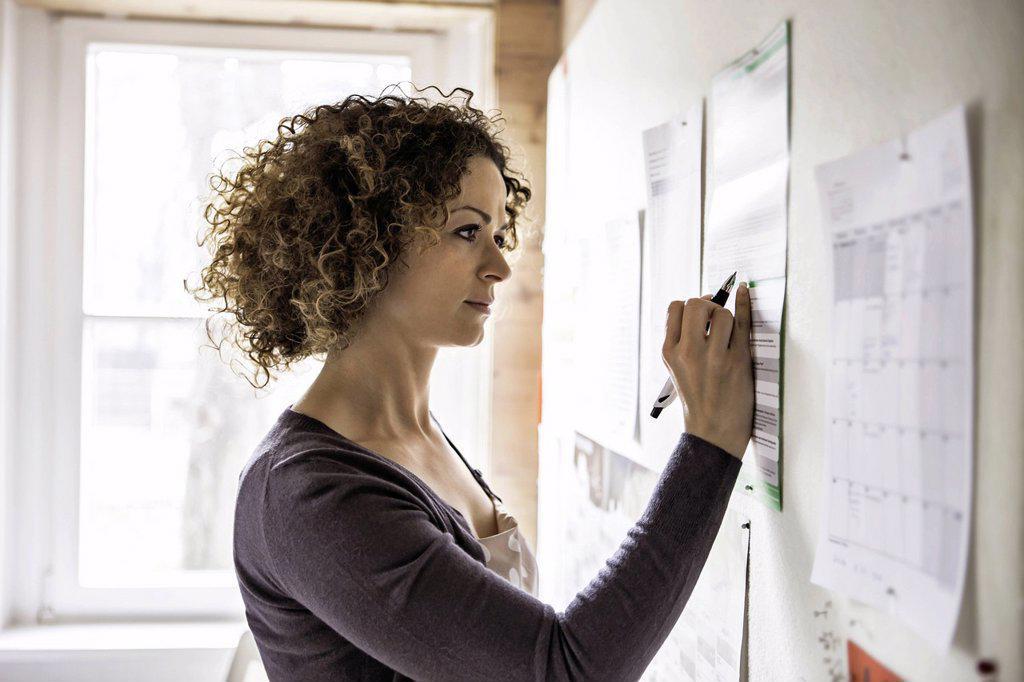 Stock Photo: 1773-88415 Businesswoman writing on sheet