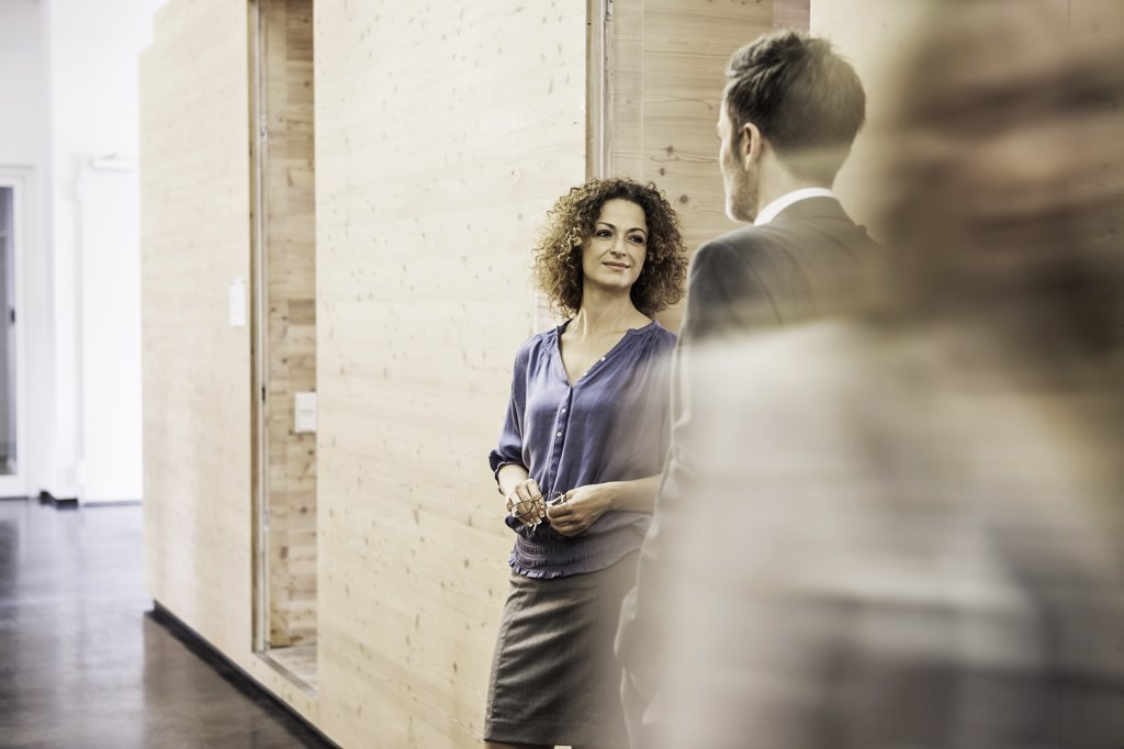 Business people standing in busy hallway : Stock Photo
