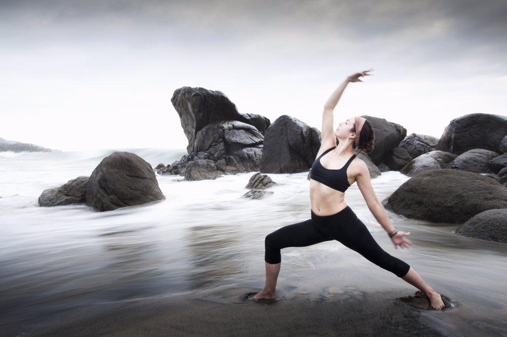 Woman practicing yoga on sandy beach : Stock Photo