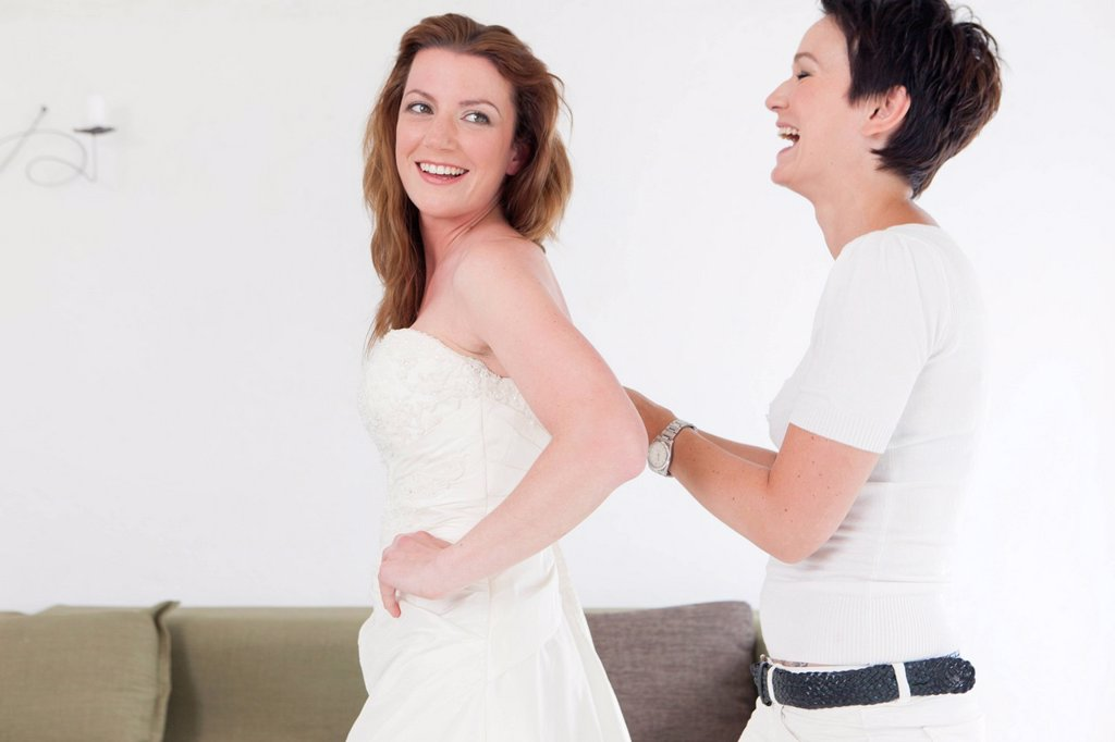 Stock Photo: 1773-88615 Designer adjusting gown on client
