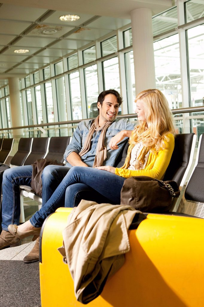Stock Photo: 1773-88689 Couple talking in airport waiting area
