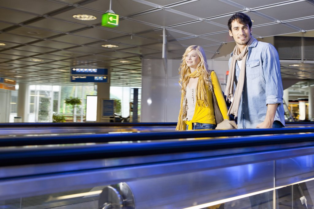Couple on moving walkway in airport : Stock Photo