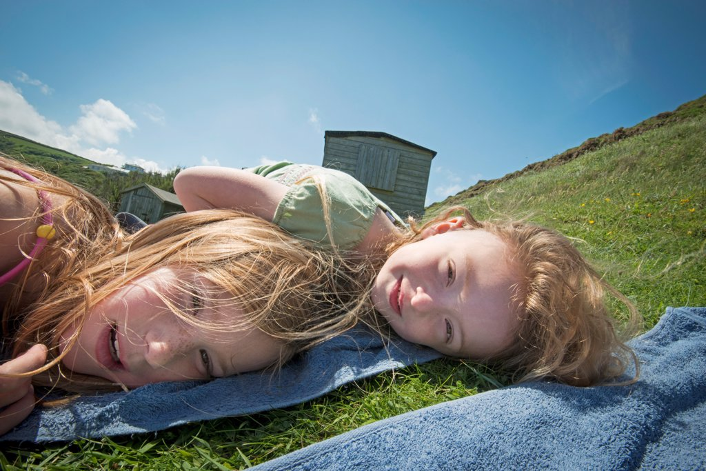 Girls laying on towels in grass : Stock Photo