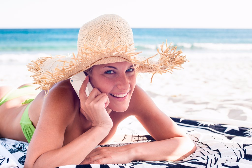 Woman talking on cell phone on beach : Stock Photo