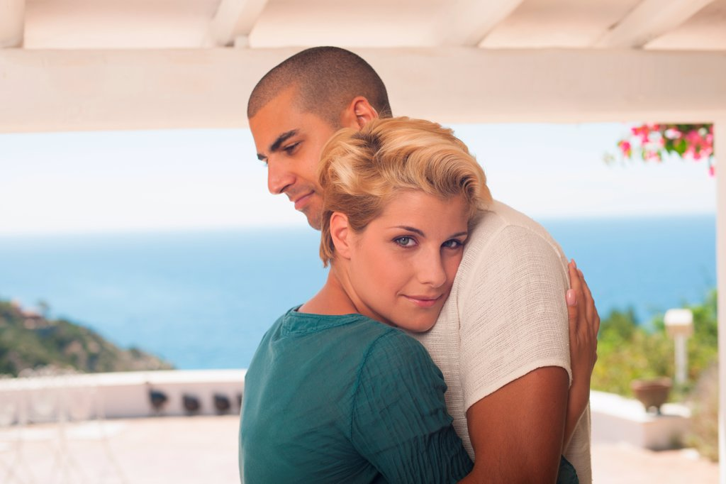 Smiling couple hugging on balcony : Stock Photo