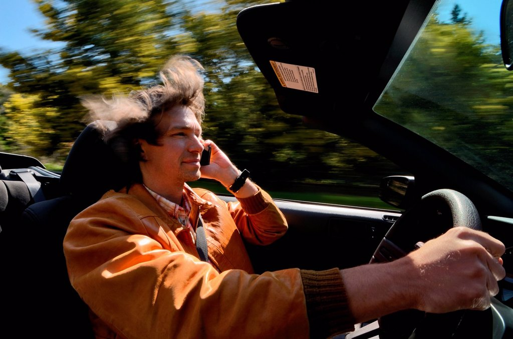 Man driving and talking on cell phone : Stock Photo