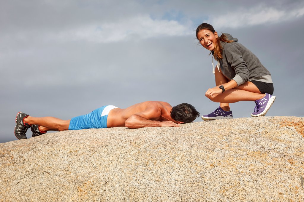 Couple laughing on boulder : Stock Photo