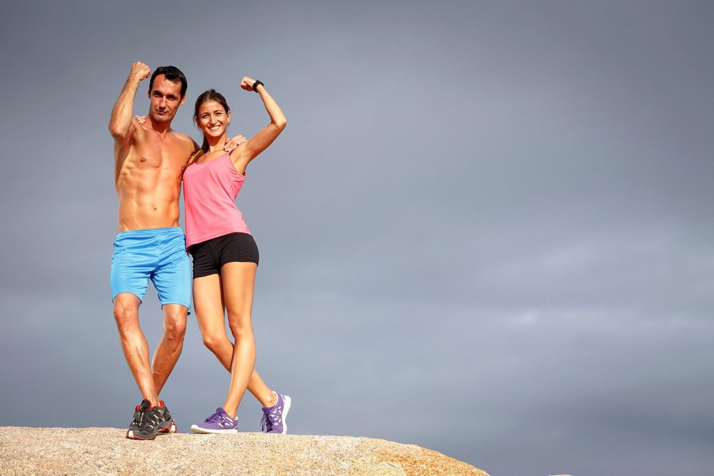 Stock Photo: 1773-99958 Couple flexing muscles on boulder