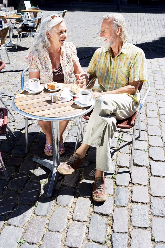 Couple sitting at café table : Stock Photo