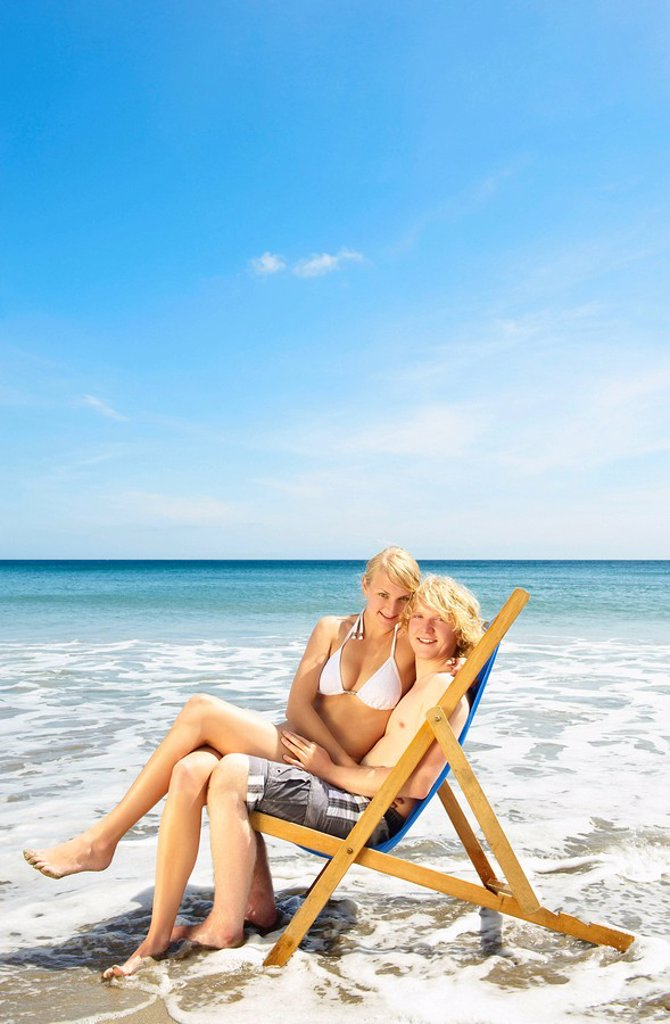Young couple sharing a deck chair : Stock Photo