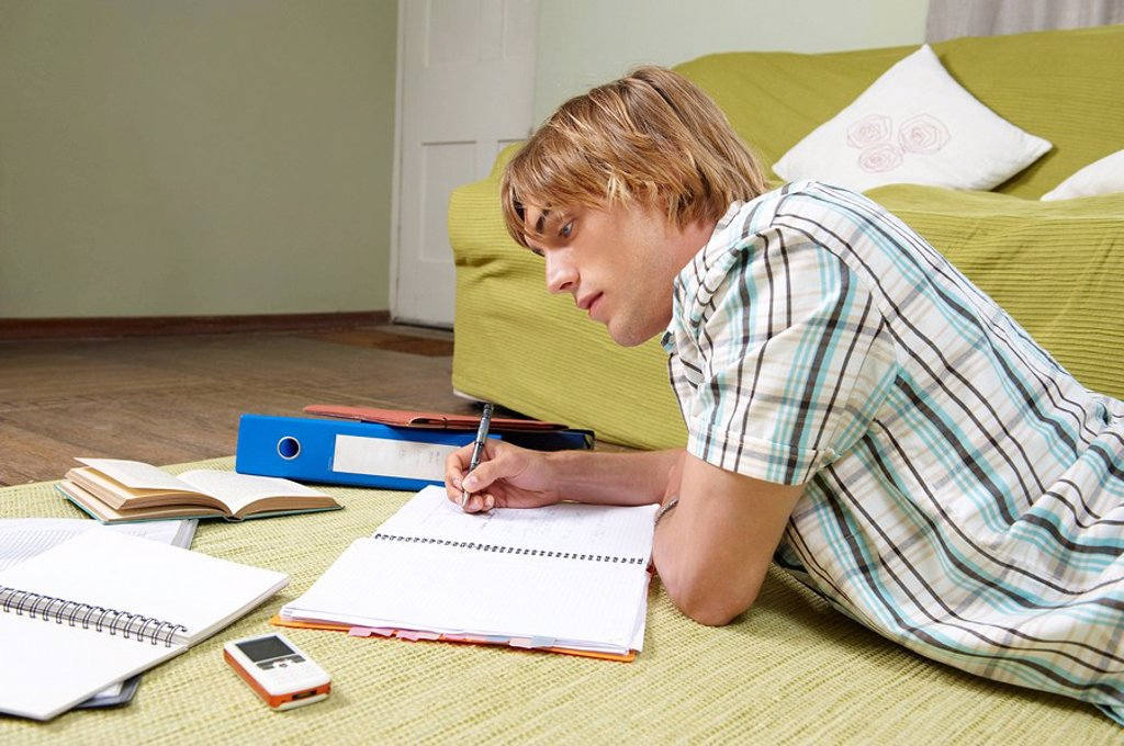 Stock Photo: 1773R-103279 Young man doing home work on rug