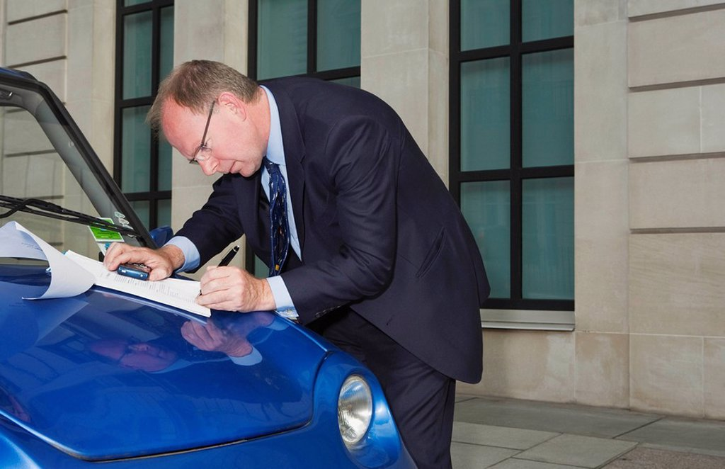 Man signing document on car bonnet : Stock Photo