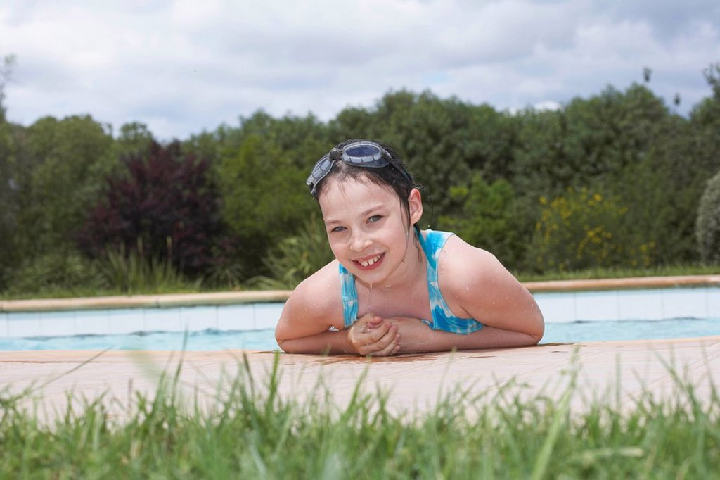 Young girl smiling by swimming pool : Stock Photo