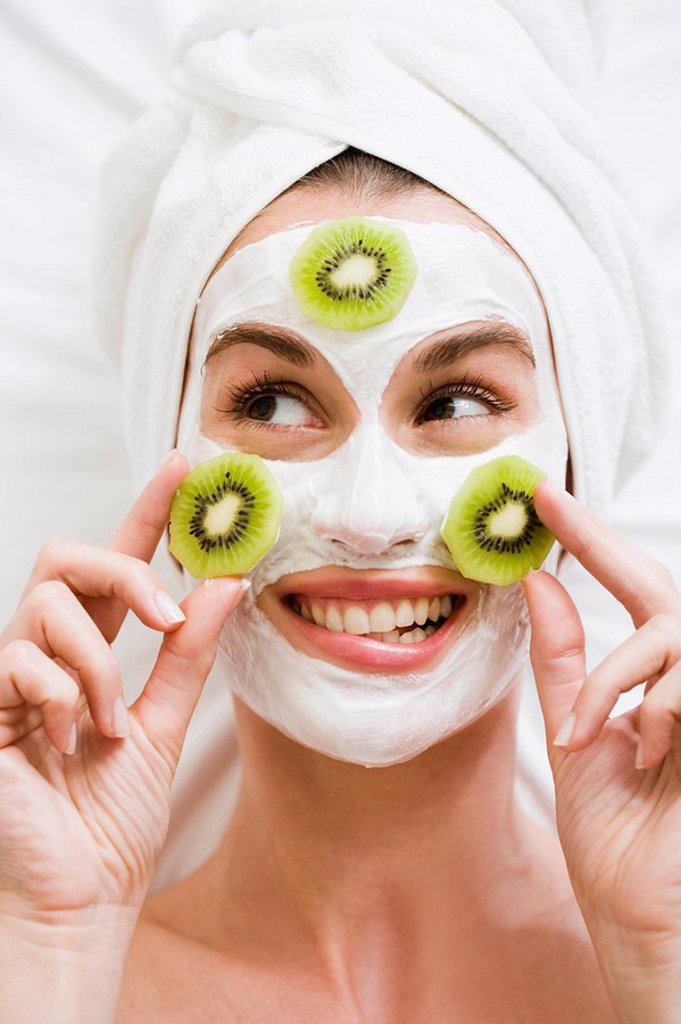 Stock Photo: 1773R-106910 Woman with face mask and kiwi fruit
