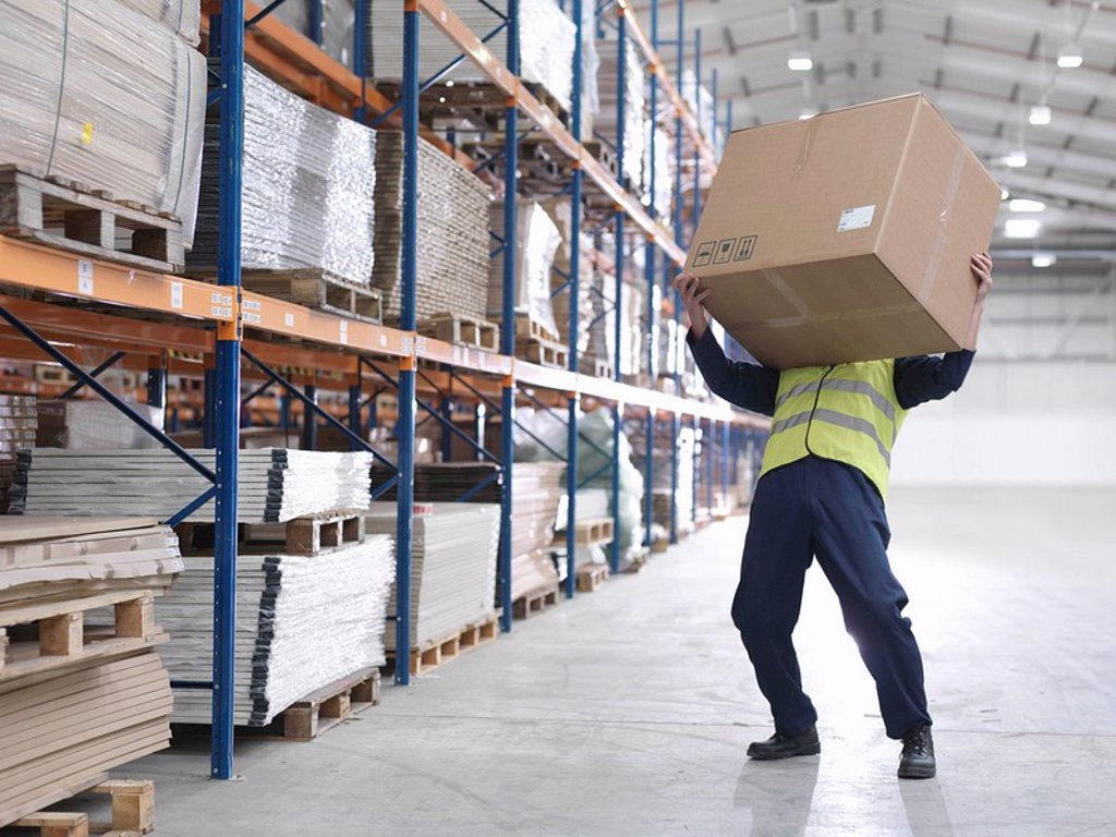 Worker Struggling With Box In Warehouse : Stock Photo