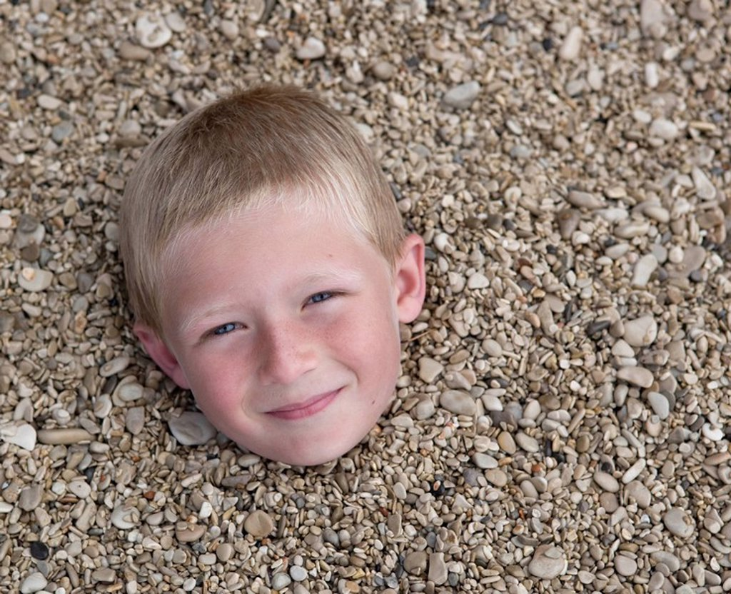 Boy buried in pebbles on beach : Stock Photo